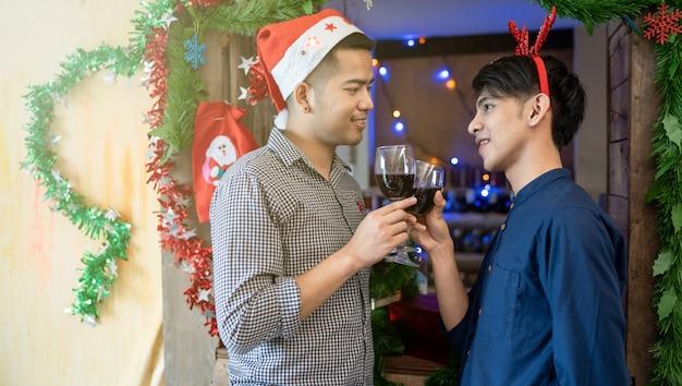 Las parejas masculinas lgbt beben vino celebra la temporada navideña