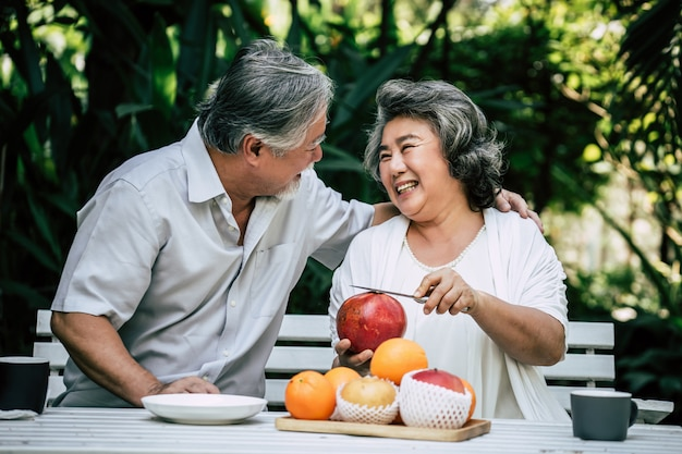 Parejas mayores jugando y comiendo algo de fruta