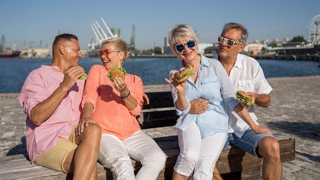 Parejas mayores en la playa comiendo hamburguesas