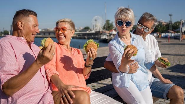Parejas mayores en la playa disfrutando de hamburguesas