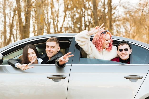Parejas posando en la ventana del coche y mostrando el gesto de paz