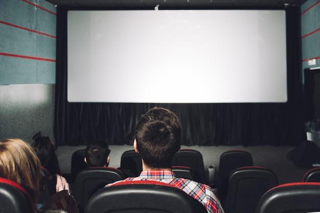 Parejas sin rostro mirando la pantalla del cine