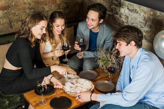 Parejas sonrientes disfrutando de fiesta con pizza y vino.