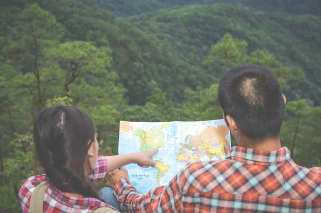 Las parejas ven un mapa en un bosque tropical con mochilas en el bosque. aventura, senderismo, escalada.
