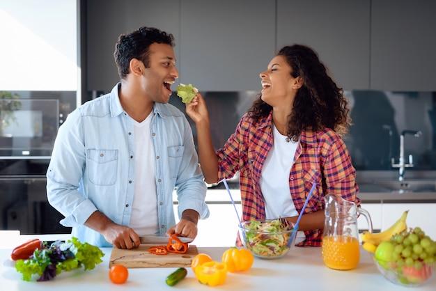 Pares afroamericanos que cocinan la ensalada en cocina.