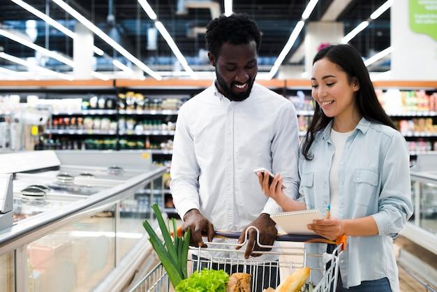Pares alegres con el carro de la compra que comprueba en lista de compras móvil en el supermercado