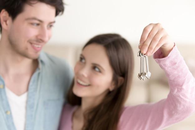 Pares alegres jovenes que llevan a cabo llaves de la nueva casa