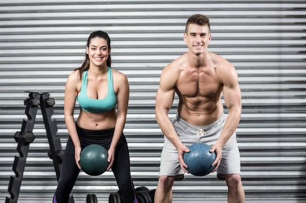 Pares aptos que hacen ejercicio de la bola en el gimnasio del crossfit