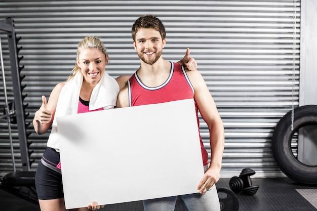 Pares aptos que sostienen el papel en blanco en el gimnasio del crossfit