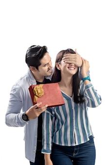Pares asiáticos jovenes que celebran día de tarjetas del día de san valentín con dar un regalo