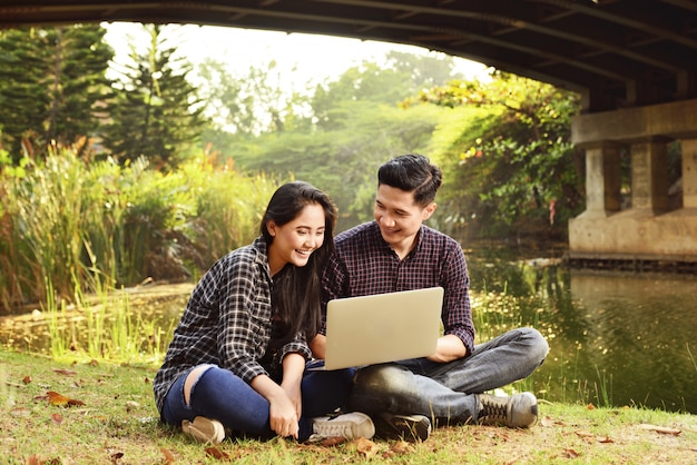 Pares asiáticos jovenes que se relajan junto con el ordenador portátil