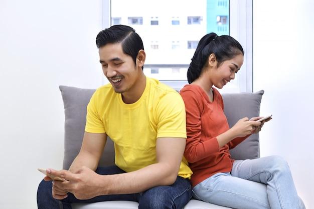 Pares asiáticos jovenes que se sientan en el sofá con el teléfono móvil