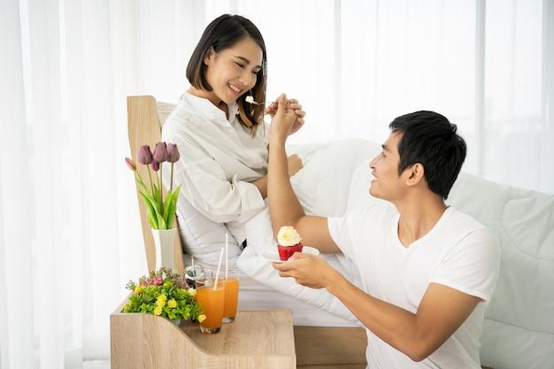 Pares asiáticos que comen una torta y un zumo de naranja en el dormitorio, concepto de pareja linda.