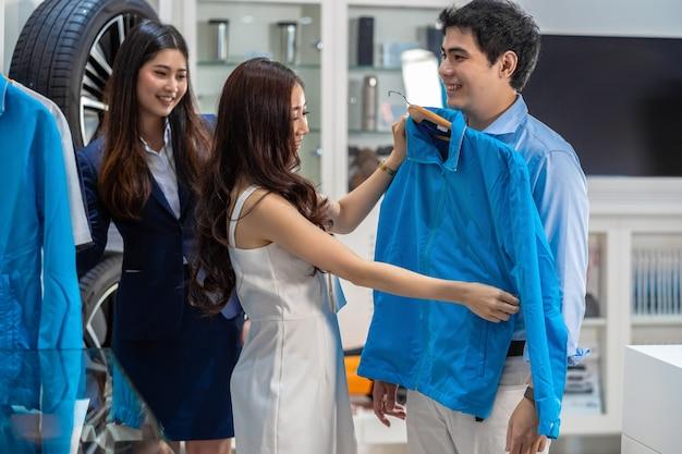 Pares asiáticos que eligen y que intentan la ropa elegante a su novio en la sala de exposición del coche,
