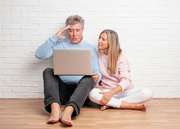 Pares bastante mayores que se sientan en su piso de la casa con una computadora portátil