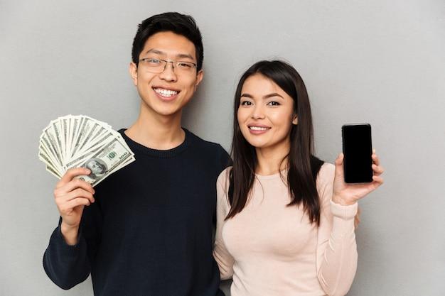 Pares cariñosos asiáticos jovenes alegres que sostienen el dinero y que muestran la exhibición del teléfono móvil.