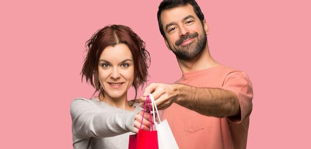 Pares en el día de san valentín que sostiene muchos bolsos de compras sobre fondo rosado aislado
