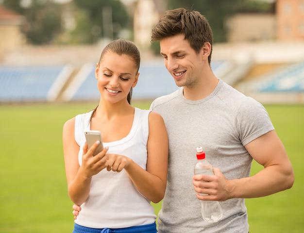 Los pares están mirando el smartphone durante ejercicios en estadio