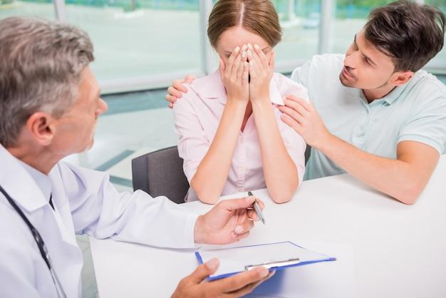 Pares de la familia que se sientan en la oficina del doctor en la consulta.