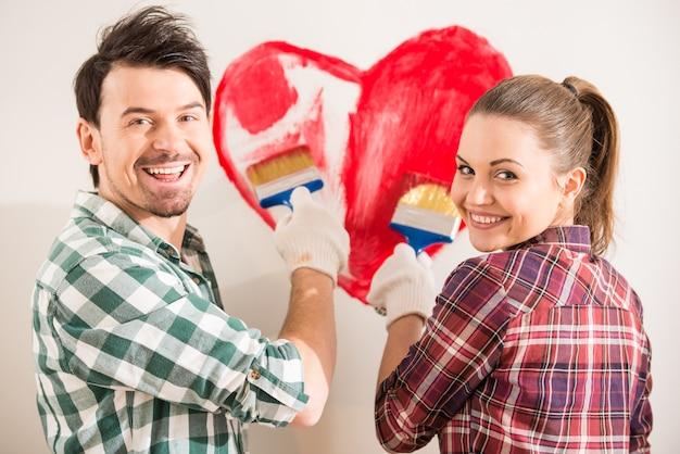 Los pares felices jovenes están pintando un corazón en la pared.