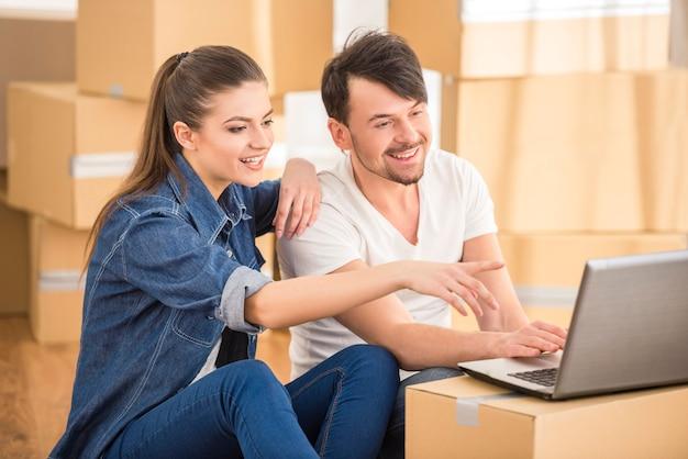 Pares felices jovenes que buscan para los apartamentos con la computadora portátil.