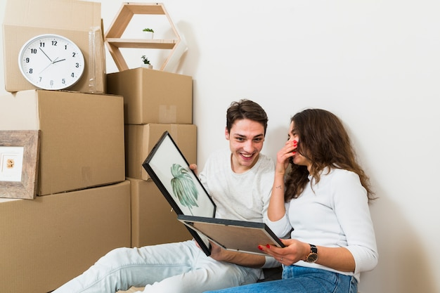 Pares felices jovenes que llevan a cabo el marco de imagen disponible con las cajas móviles en el nuevo hogar
