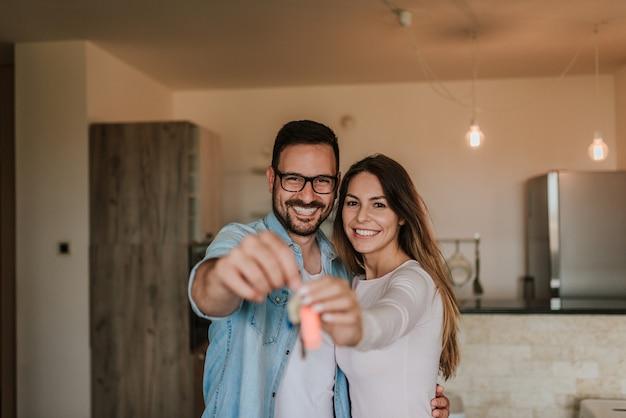 Pares felices jovenes que muestran llaves del nuevo hogar. mirando a la camara