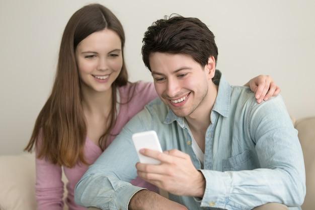 Pares felices jovenes que se sientan en el sofá en casa usando smartphone
