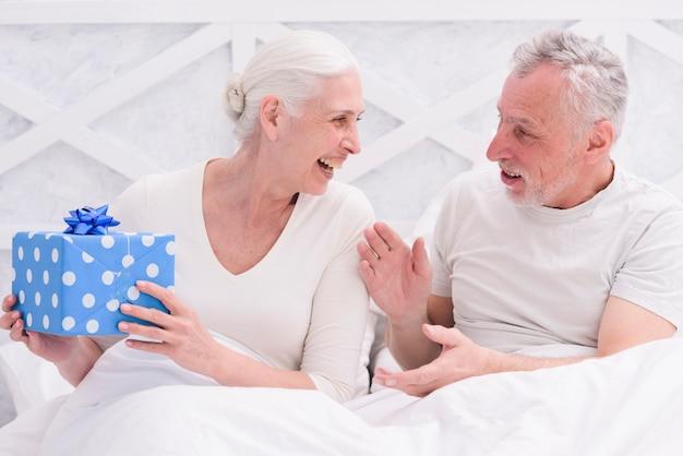 Pares felices mayores que se sientan en la cama que sostiene la caja de regalo azul
