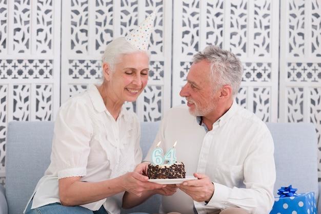 Pares felices mayores que sostienen la torta de cumpleaños con la vela