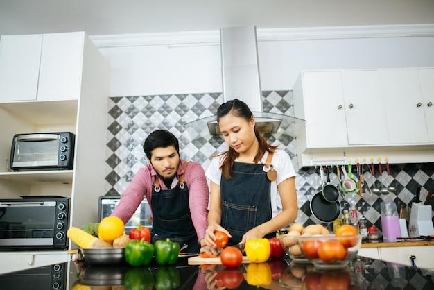 Pares felices que cocinan junto en la cocina en casa.