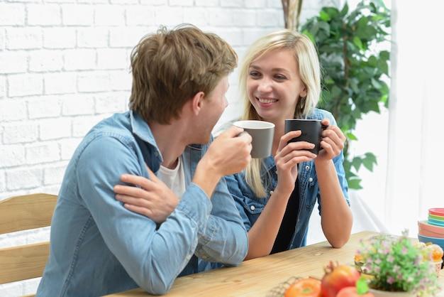 Pares felices que comen el descanso para tomar café y el postre en la cocina blanca.