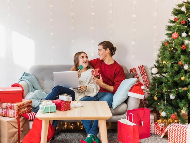Pares felices que se sientan con el ordenador portátil y la tarjeta de crédito en el sofá