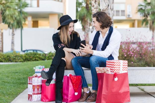 Pares felices que se sientan con smartphone en banco