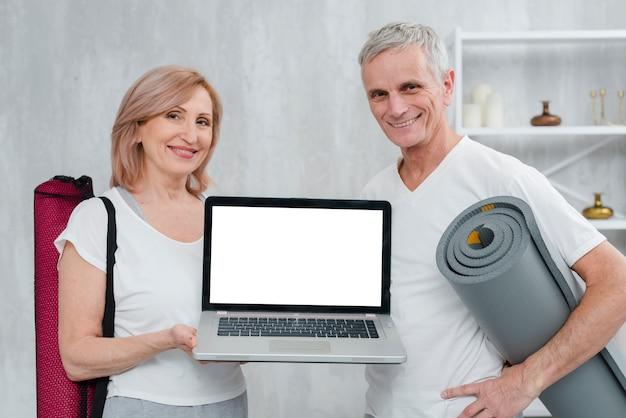 Pares felices que sostienen la estera y el ordenador portátil de la yoga con la pantalla blanca en casa