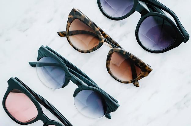 Pares de gafas de sol redondas sobre un fondo blanco.