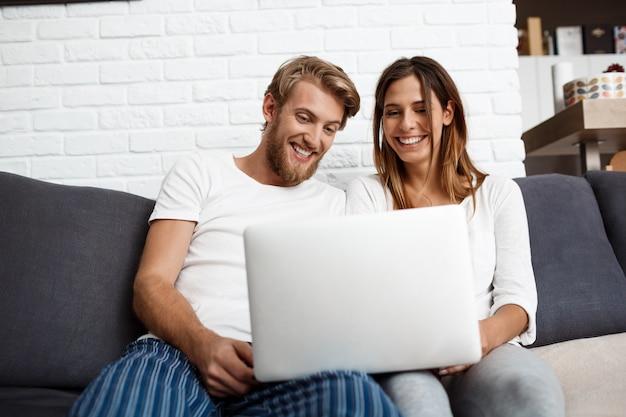 Pares hermosos que miran la sentada sonriente de la computadora portátil en hogar del sofá.