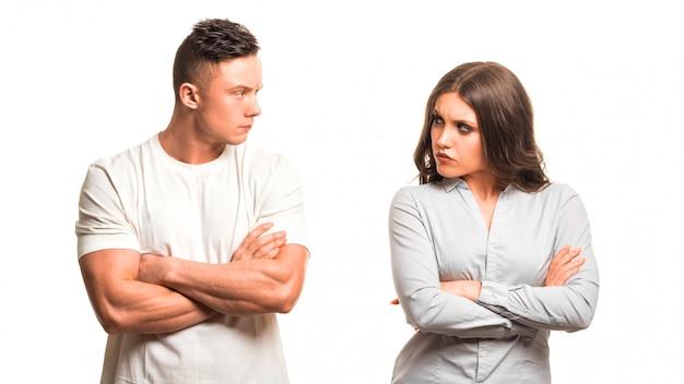 Pares infelices que sostienen los brazos cruzados y que se miran aislados en el fondo blanco. concepto de psicología familiar.