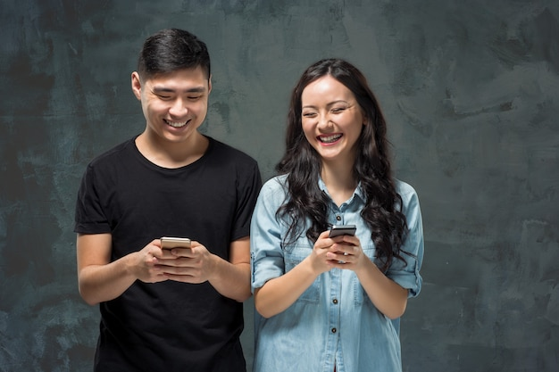 Pares jovenes asiáticos que usan el teléfono celular, retrato del primer.