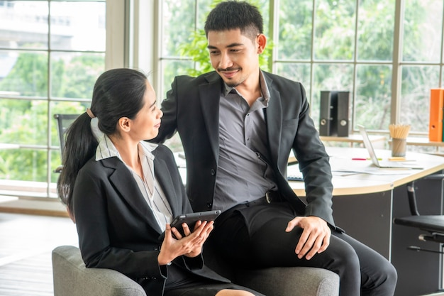 Los pares jovenes asiáticos del retrato se sientan en el sofá juntos, concepto del negocio