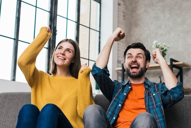 Pares jovenes emocionados que se sientan en el sofá que anima con alegría en casa