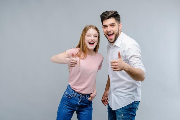 Pares jovenes felices del hombre y de la mujer que muestran los pulgares para arriba aislados sobre fondo gris