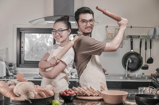 Pares jovenes felices que cocinan en la cocina, actividad asiática de los pares en cocina.