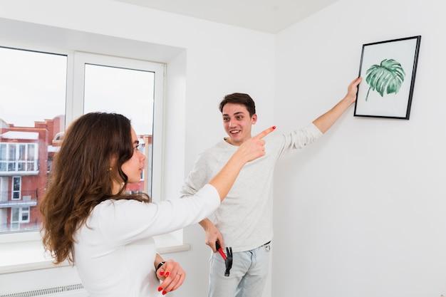 Pares jovenes felices que eligen el lugar para el marco de imagen en sala de estar en casa