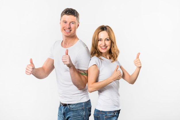Pares jovenes felices que muestran el pulgar encima de la muestra contra el fondo blanco