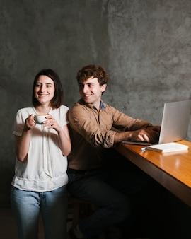 Pares jovenes felices que trabajan en la computadora portátil