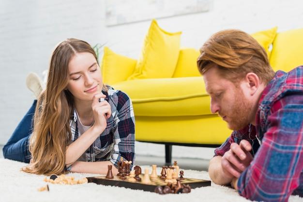 Pares jovenes que mienten en la alfombra que mira el tablero de ajedrez en la alfombra blanca en casa