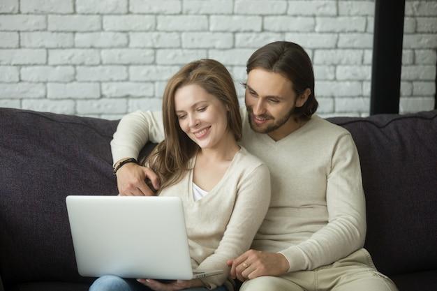 Pares jovenes que se sientan en el sofá que abraza usando el ordenador portátil en casa