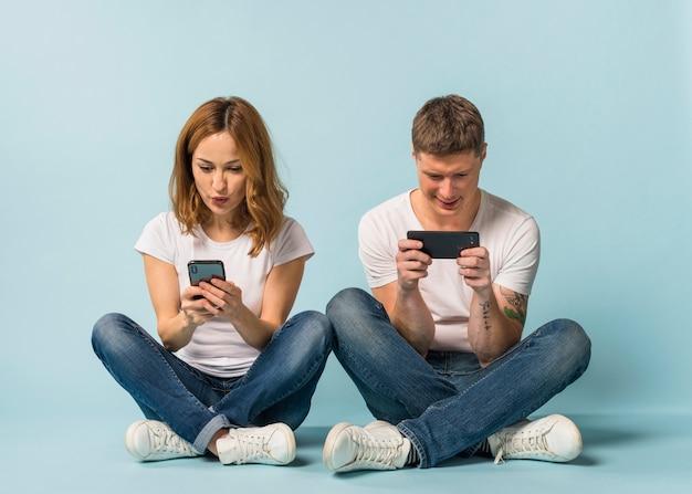 Pares jovenes que se sientan en el vídeo de observación del piso en el teléfono móvil contra el contexto azul