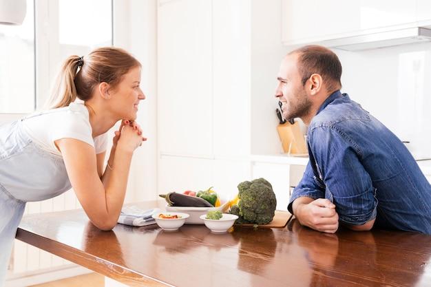 Pares jovenes sonrientes que se miran con las verduras frescas en la tabla en la cocina